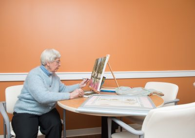A resident painting a picture in the art room at Scott-Farrar Independent & Assisted Living in Peterborough, NH