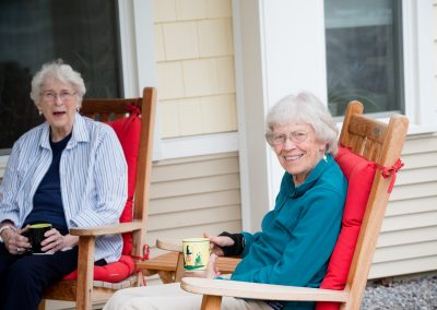 Two women at Scott-Farrar sitting in chairs enjoying a conversation