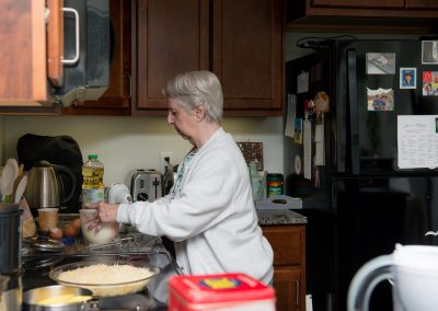 An independent living resident preparing a meal in their own kitchen at Scott-Farrar